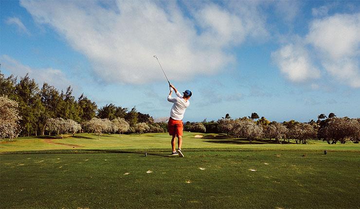 ゴルフでティーショットを打つ男性